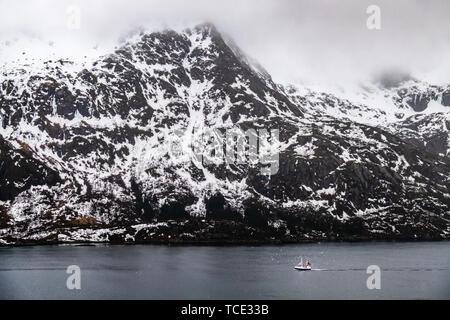 Boat sailing past a snowcapped mountain, Lofoten, Nordland, Norway - Stock Image