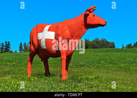 CowParade cow painted in the style of the Swiss national flag with the Swiss cross, Hirzel, Switzerland - Stock Image
