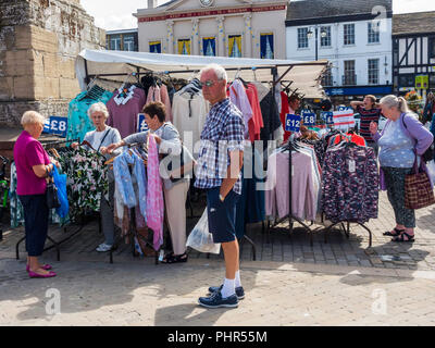 A group of ladies shopping for dresses in Ripon Market North Yorkshire while a man waits patiently - Stock Image
