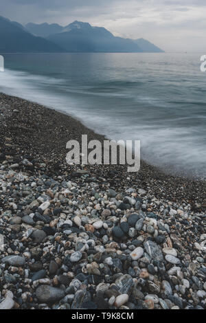 Waters of the Pacific Ocean washing over the pebbles, Central Mountain Range on background, Chisingtan Scenic Area, Hualien County, Taiwan - Stock Image