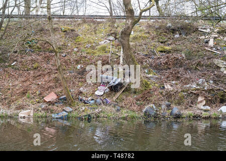 fly tipping scotland - rubbish thrown from the road onto the bank of the Forth and Clyde Canal near Kirkintilloch, Scotland, UK - Stock Image