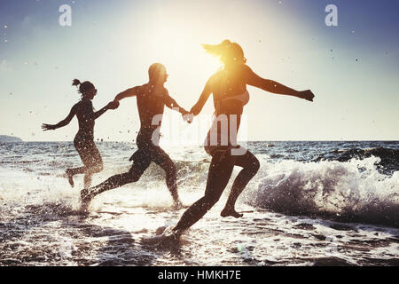 Happy friends beach sunny sea - Stock Image