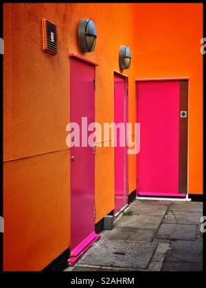 Three bright pink doors surrounded by an orange wall. Bright urban colours in a concrete jungle?! A side alleyway out of sight? Photo Credit - © COLIN HOSKINS. - Stock Image