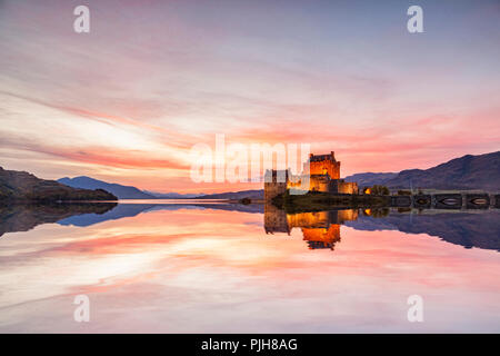 Eilean Donan Castle illuminated at twilight, Highland, Scotland, UK, reflected in the waters of Loch Duich. - Stock Image