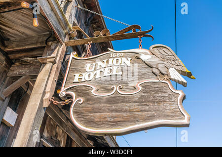 An old carved wooden sign for the historic Union Hotel in Los Alamos, California hangs from the front of the hotel over the wooden sidewalk. - Stock Image