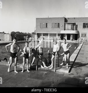 1950s, boys standing by an outdoor swimming pool at the sports club of the brickworks of the London Brick Company at Stewartby, Bedford, England. The company was a paternal employer and as well as many social facilities, the company provided their workers with quality brick-built housing. - Stock Image