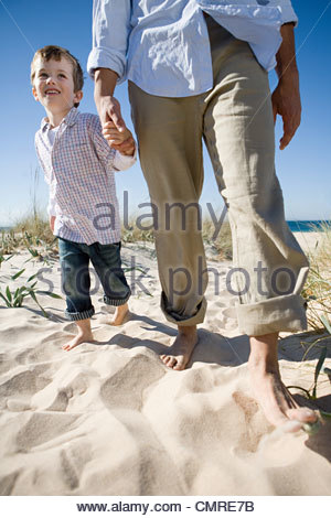 Boy at beach with father - Stock Image