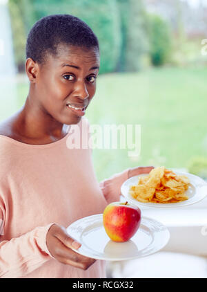Ethnic girl undecided whether to have crisps or an apple to eat - Stock Image