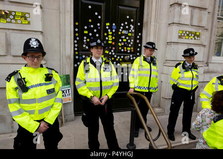 London, UK. 23rd June 2018. Police protecting the doors to the Cabinet Office in Whitehall after they had been festooned with anti-Brexit stickers - March for a Peoples Vote.  Credit: Scott Hortop/Alamy Live News. - Stock Image