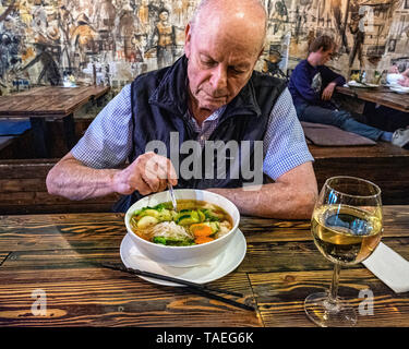 Fam Dang Vietnamese restaurant interior in Torstasse, Mitte-Berlin. Senior elderly man eating bowl of soup - Stock Image