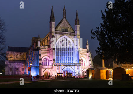 Gothic Winchester Cathedral illuminated at night and Winchester Christmas market - popular tourist attractions in the former capital city of England - Stock Image