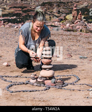 Dunbar, East Lothian, Scotland, UK. 21st Apr 2019. European stone stacking championship:  Brioney Maclean, from Wales, balances stones in the artistic competition, giving competitors 3 hours to create anything from stones or found objects at Eye Cave beach on the second day which comprises 2 competitions, a 3 hour artistic challenge and a children's competition.. The overall winner receives a trip to llano Earth Art Festival & World Stone Balancing competition in Texas in 2020. Credit: Sally Anderson/Alamy Live News - Stock Image