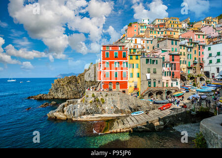 The colorful coastal village, boat lanch and harbor or Riomaggiore Italy on a pretty summer day on the Ligurian Coast. Part of the Cinque Terre - Stock Image