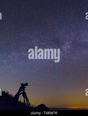 Silhouette of a camera and tripod taking photographs of the Milky Way, Cornwall, UK - Stock Image