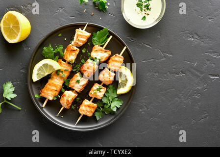 Barbecue salmon skewers on black stone background with copy space. Top view, flat lay - Stock Image