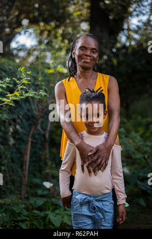 Granddaughter standing in front of grandmother in a garden - Stock Image