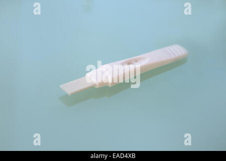 Pregnancy testing stick on a green table top. - Stock Image