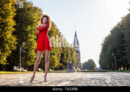young beautiful woman in red dress standing on the alley in the park on sunny summer day - Stock Image