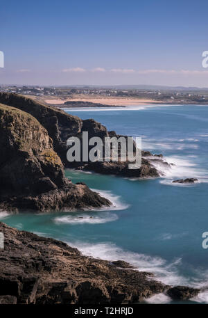 Dramatic cliff edges at DInas Head on the north Atlantic coast, with Boobys Bay beach in the background, Cornwall, England, UK - Stock Image
