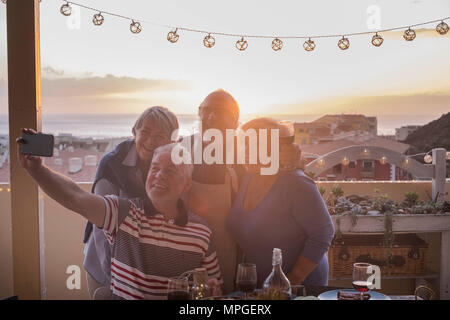 Group of four people friends enjoying food on the terrace field. Bright sunset and horizon over the ocean. - Stock Image