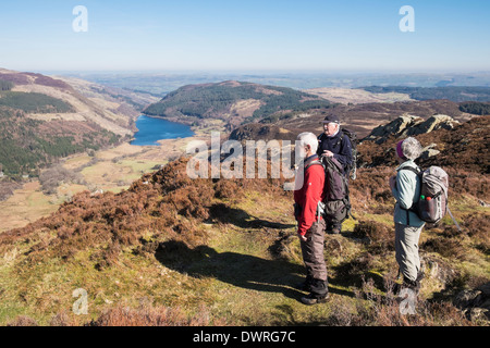 Three walkers on Crimpiau hilltop with a view to Llyn Crafnant lake in valley in Snowdonia National Park, Conwy, North Wales, UK, Britain - Stock Image