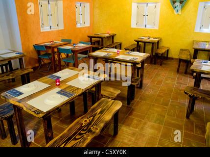 The rustic-styled interior of Sitio da Pedralva restaurant, located at Aldeia da Pedralva tourist village in the - Stock Image