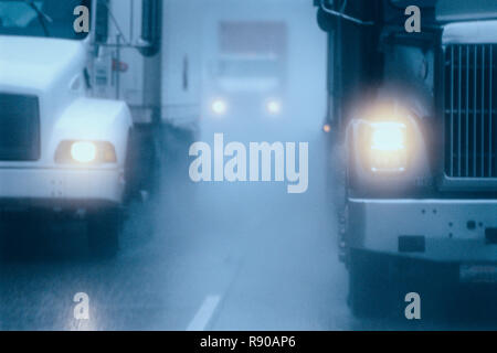 Partial view of large commercial truck driving in hazardous conditions of snow and rain on a freeway. - Stock Image