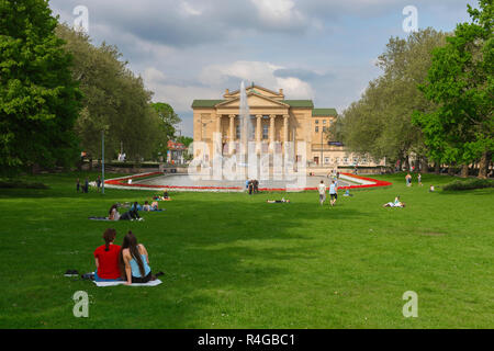 Park city summer, view in summer of people relaxing in the Park Mickiewicza looking towards the Poznan city theatre building (Teatr Wielki), Poland - Stock Image
