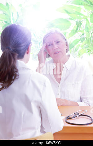 Female doctor with her senior patient with sleeping trouble, suffering of splitting headache or migraine, copy space - Stock Image