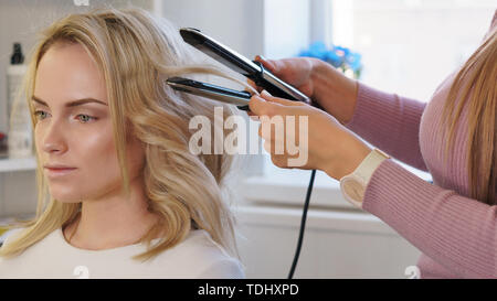 Hairdresser makes hairstyle to client. Delicate and fun customer service. Beauty industry. Creation of evening hairstyles fashionable stylish women's  - Stock Image