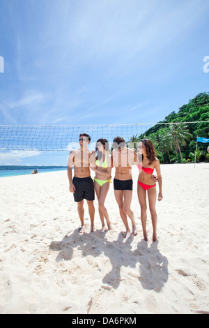 Friends playing on a beach. - Stock Image