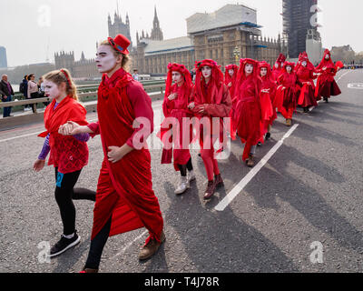 London, UK. 17th April 2019. A group dressed in bright red for the blood of the species which will become extinct  processes across Westminster Bridge. Two days after Extinction Rebellion blocked the roads in Parliament Square it remains closed to traffic. Activities continue in and around the square with new protesters arriving. Credit: Peter Marshall/Alamy Live News - Stock Image