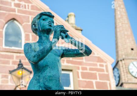 A close up view of a statue of Peter Pan on Glengate in Kirriemuir in Sctoalnd in memory of  Sir J M Barrie who was born in Kirriemuir. - Stock Image