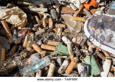 Cigarette stubbs and fag ends in a public ashtray - Stock Image