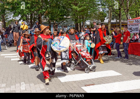 Vancouver, Canada.1st July, 2018. A group of Canadian First Nations people chant and walk  in the annual Canada Day Parade on Granville Island, Vancouver, British Columbia. This year Canada Day celebrates the country's 151st birthday. Credit: John Mitchell/Alamy Live News - Stock Image