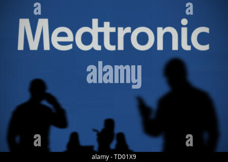 The Medtronic logo is seen on an LED screen in the background while a silhouetted person uses a smartphone in the foreground (Editorial use only) - Stock Image