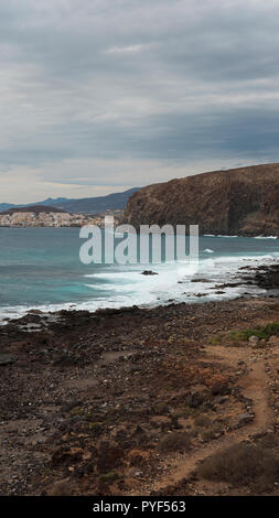 Narrow, vertical perspective of coastal landscape with Los Cristianos resort in the background, from Palm-Mar, Tenerife, Canary Islands, Spain - Stock Image