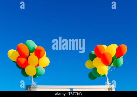 colorful balloons on a blue sky background. - Stock Image
