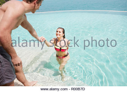 Young couple getting out of swimming pool - Stock Image