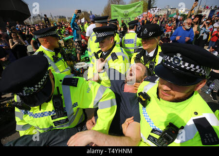An Extinction Rebellion demonstrator is carried away by police on Waterloo Bridge in London. - Stock Image