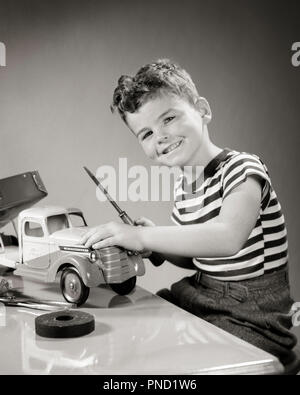 1940s SMILING BOY LOOKING AT CAMERA PLAYING WITH TOY TRUCK DOING REPAIRS WITH SCREWDRIVER - j10555 HAR001 HARS REPAIRS SMILES FRIENDLY JOYFUL SCREWDRIVER JUVENILES BLACK AND WHITE CAUCASIAN ETHNICITY HAR001 OLD FASHIONED - Stock Image