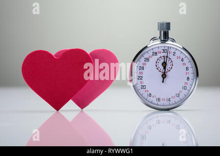 Reflection Of Red And Pink Heart Shape With Stopwatch On White Desk - Stock Image