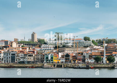 Porto, Portugal - April 28, 2019: Bars and restaurants old town skyline of Vila Nova de Gaia from across the Douro River - Stock Image
