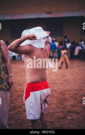 Mali, Africa - Young caucasian man volunteer wearing a white t-shirt uniform while playing soccer with black african children, boys and adults in a ru - Stock Image