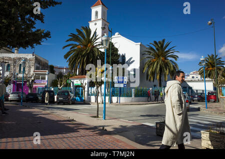 Chefchaouen, Morocco : A man wearing a djellaba walks at Mohamed V square with the former Spanish church in background. - Stock Image