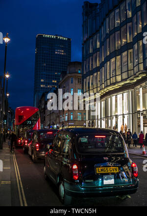 Black cabs and London double decker bus Oxford street at night with Centre Point tower in background - Stock Image