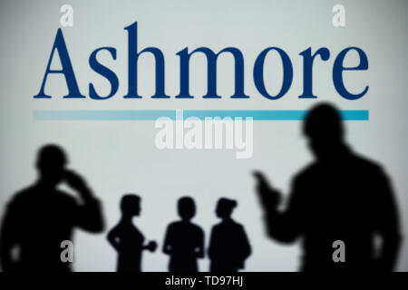 The Ashmore logo is seen on an LED screen in the background while a silhouetted person uses a smartphone in the foreground (Editorial use only) - Stock Image