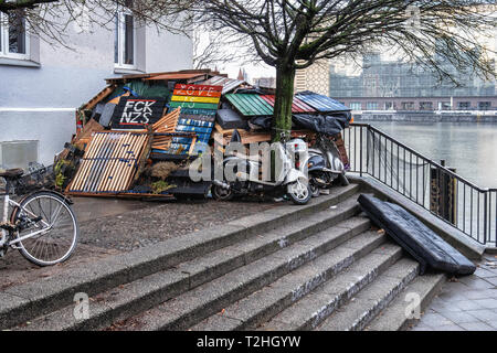 Berlin, Kreuzberg. Informal dwelling next to the river Spree made of recycled, reclaimed materials. Two parked scooters for transport - Stock Image