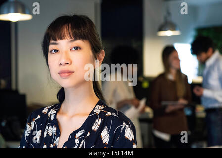 Serious businesswoman standing in office - Stock Image