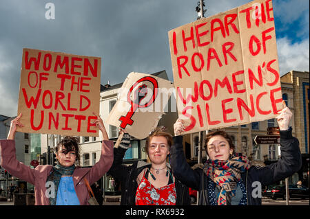 Cork, Ireland. 8th March, 2019. Khadijha Bracken, Ida Wulff and Luna Rave, representing the Connolly Youth Movement, hold up placards at a '#Walkout 4 Equality' protest on International Women's Day on Patrick Street, Cork. The women are protesting sexual violence, the 14%pay gap and the cervical check scandal, as well as other issues. Credit: Andy Gibson/Alamy Live News. - Stock Image